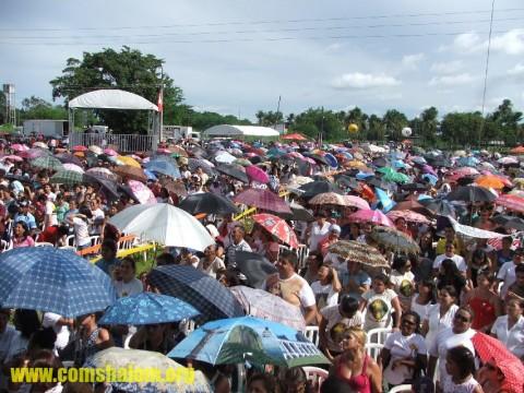 A multidão se protegia do sol como podia