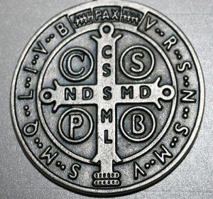 Detalhe da medalha de São Bento. Exorcismo católico acontece mediante permissão do bispo local.