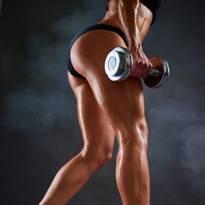 Low section of young woman in perfectly fit shape doing weight training