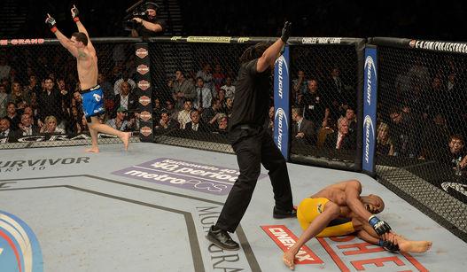 Anderson caído no chão após lesão e Weidman celebrando a manutenção do título. UFC. Foto: UFC/Divulgação