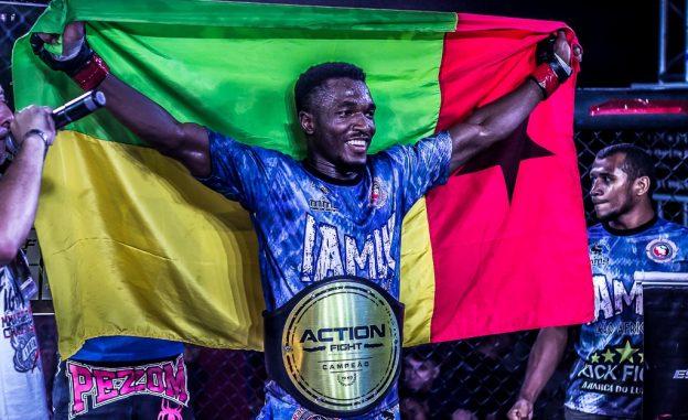 Iamik exibe com orgulho a bandeira de seu país ao ser coroado campeão do Action Fight. Foto: Alex Zenon/Divulgação