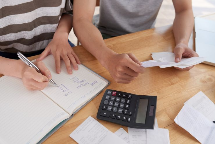 Mãos de pessoas com bloco de notas, calculadora e caneta, em posição de cálculo de dívidas