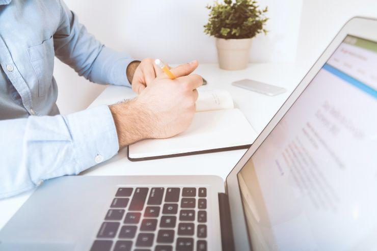 Homem tomando notas ao lado de notebook; aprenda a fazer um planejamento operacional e financeiro