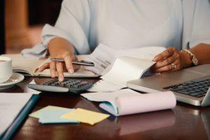 Mãos de mulher olhando contas e usando a calculadora; apps podem ajudar pequeno empreendedor