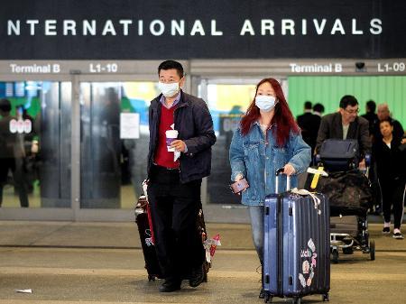 Viajantes de máscara por conta do coronavírus