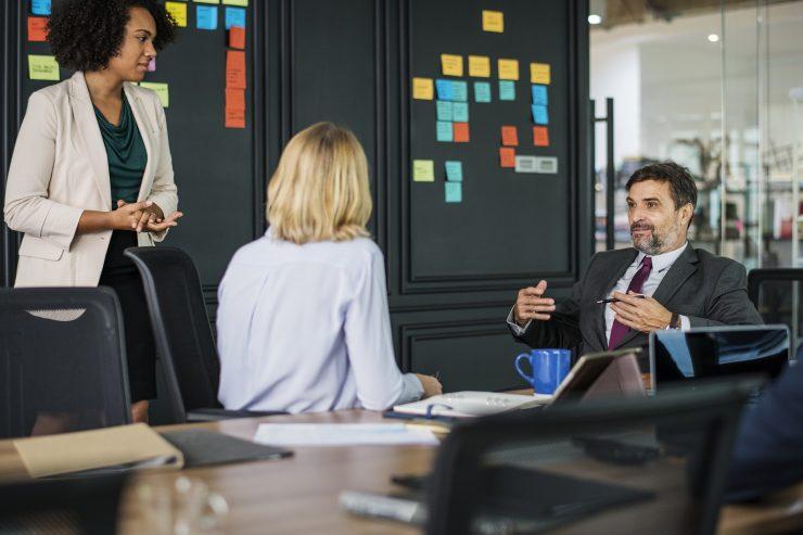Um homem e duas mulheres conversam sobre negócios. Eles estão em frente a uma lousa preta repleta de post-its coloridos
