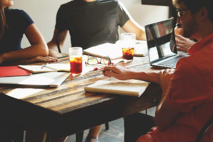 Três pessoas se reúnem em uma sala, enquanto conversam. Há um notebook sobre a mesa, junto com dois copos de bebidas