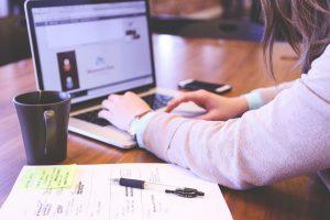 Mulher trabalha no notebook. Ao seu lado, uma xícara de café e um caderno com anotações.