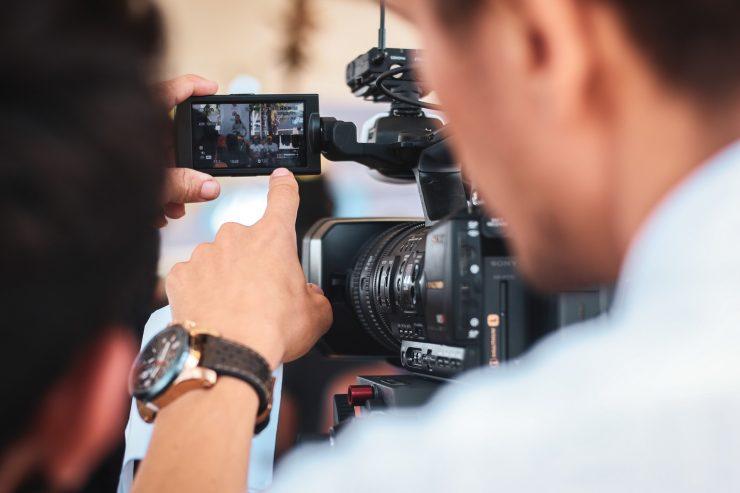 Homem trabalha com câmera de vídeo. Aponta para o visor, que filma uma cena. Produtor audiovisual.