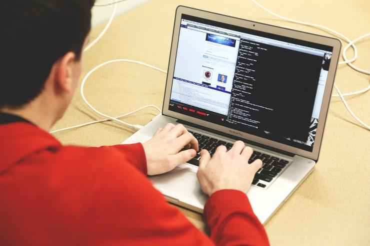 Homem de camisa laranja realiza a programação de um site em um notebook. A tela exibe diversas linhas de código.