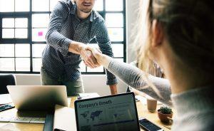 Um homem vestido de blusa azul comprida aperta a mão de uma mulher loira, com blusa cinza comprida. Estão em um escritório, cada um com notebook diante de si.