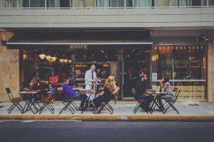 Foto da frente de um restaurante. Três mesas na frente. A da esquerda está vazia; a do centro possui um homem branco de camisa roxa e uma mulher loira de vestido preto. Na última mesa, um homem de preto conversa com uma mulher de cinza.