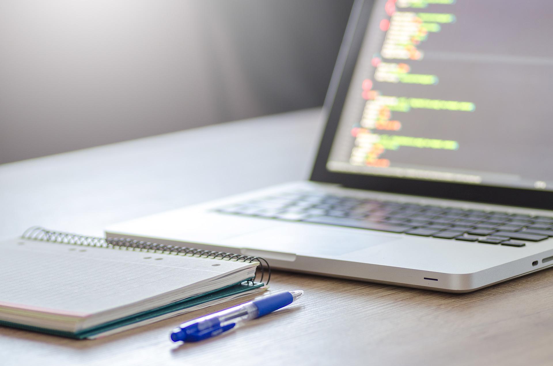 Imagem mostra um notebook, uma caneta azul e um caderno ao lado dela. A tela do computador está desfocada.
