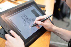 Homem desenha em tablet um personagem utilizando uma caneta específica para o equipamento.