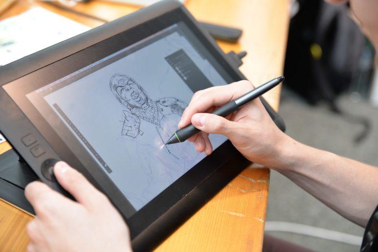 Homem desenha em tablet um personagem de quadrinhos utilizando uma caneta específica para o equipamento.