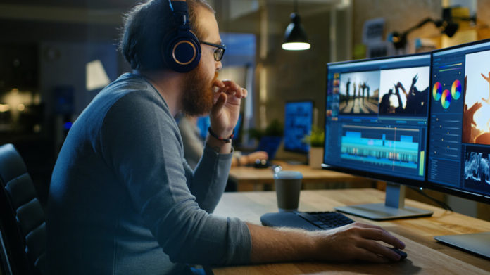 Homem ruivo e calvo utiliza computador para edição de vídeos