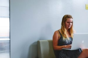 Mulher branca e loira utiliza um notebook sentada em um escritório. As paredes são cinzas e ela está concentrada.