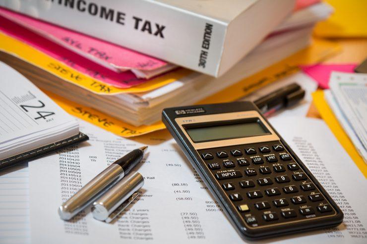 A imagem mostra uma calculadora preta, em cima de vários documentos fiscais. Ao lado, uma caneta prateada está destampada. O fundo da imagem mostra livros de finanças escritos em inglês.