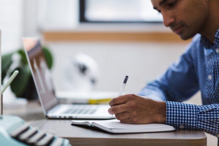 Homem de camisa comprida azul utiliza o notebook, enquanto realiza anotações em um caderno.