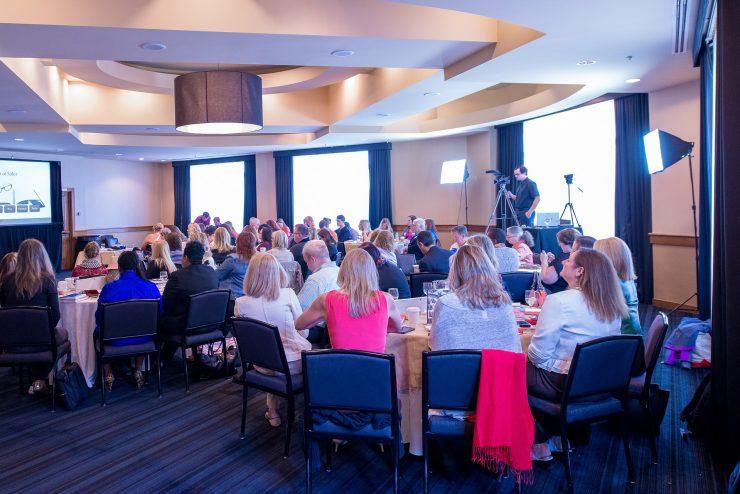 Palestra reúne dezenas de pessoas. 3 mesas lotadas com participantes. Ao lado direito da imagem, um homem de roupa preta faz a filmagem do evento.