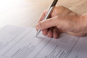 Mão de homem preenche um formulário com diferentes alternativas.