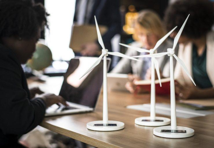 pessoas à mesa e miniaturas de postes eólicos, como forma de ilustrar sustentabilidade na empresa