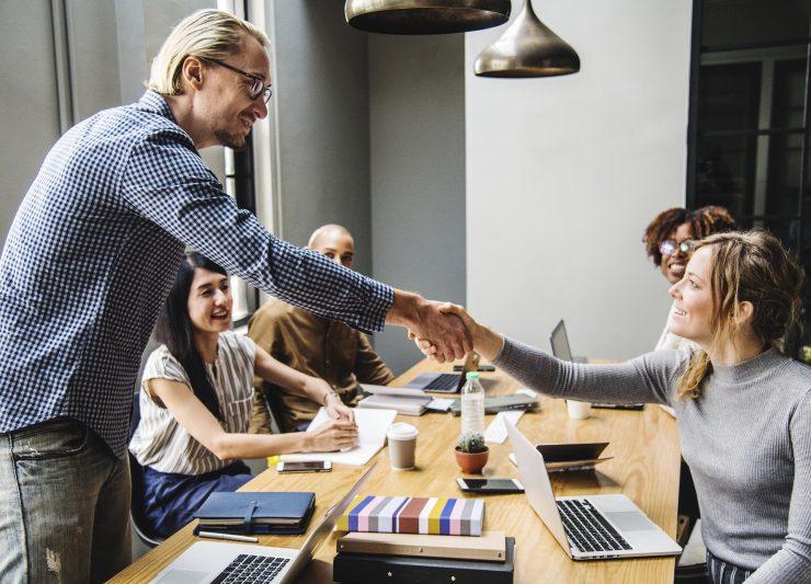 Imagem mostra uma sala de reunião com diversas pessoas. Ao centro, um homem branco de óculos aperta a mão de uma mulher loira, como firmando uma parceria entre dois fornecedores