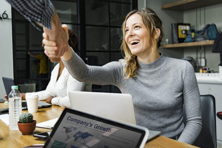 Imagem mostra uma mulher caucasiana e loira apertando a mão de um homem em uma sala. Simulam investidores anjo. Ao lado da mulher, a tela de um notebook mostra um gráfico de crescimento empresarial