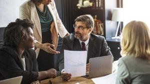 Imagem mostra 4 executivos, um homem e três mulheres, conversando, como se estivessem avaliando a alta rotatividade de uma empresa. O homem está no centro e segura uma folha com um relatório.