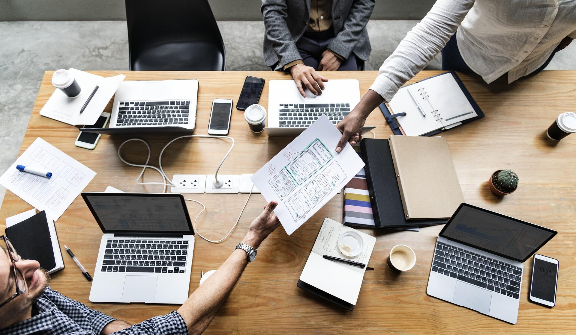 Imagem mostra uma mesa de trabalho com diversos notebooks e várias pessoas. A visão é aérea. No centro, uma pessoa passa um relatório para outra. O objetivo é ilustrar um POP.