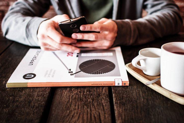 Imagem mostra as mãos de um homem utilizando um smartphone. Ao lado está uma xícara de café e em frente um livro.