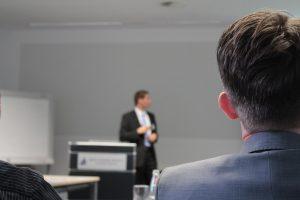 Imagem mostra um homem grisalho sentado. Ao fundo, outro homem de terno dá uma palestra, ilustrando capacitação