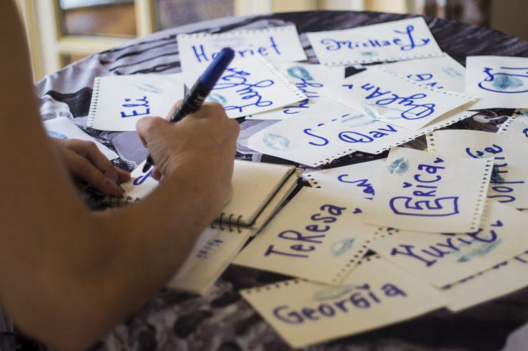 A imagem mostra uma pessoa escrevendo diferentes nomes sobre papéis em branco, como se estivesse definindo uma persona