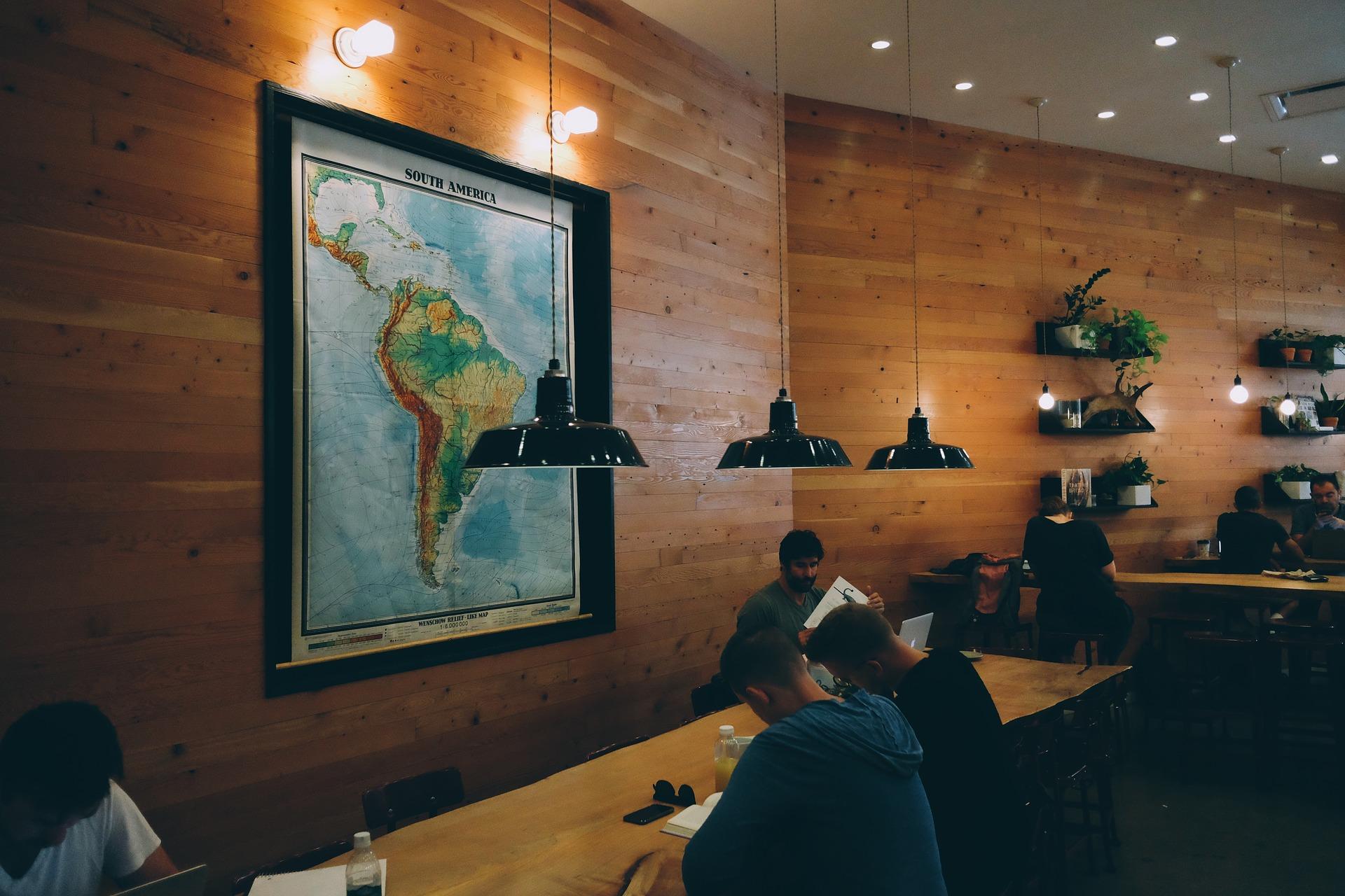 A foto mostra uma sala com várias pessoas estudando. Elas dividem uma longa mesa de madeira. Ao centro, um grande mapa com a foto da América Latina.