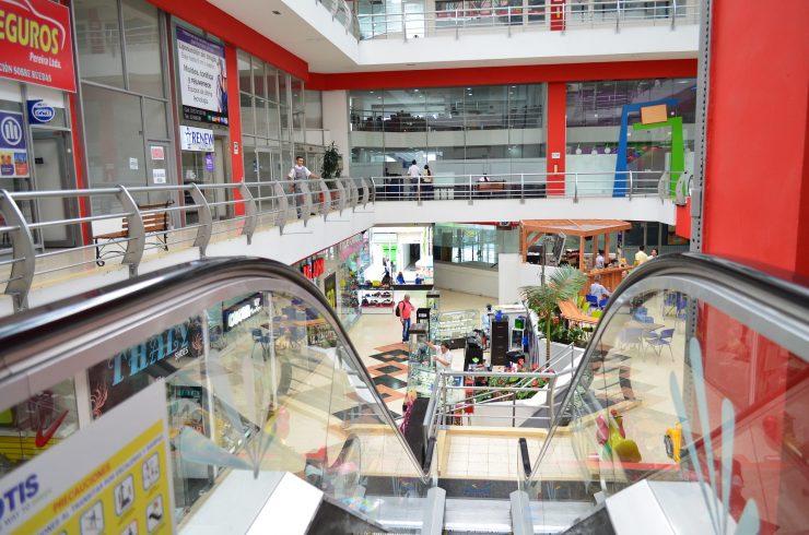 Imagem mostra o corredor de um shopping. No centro, há uma escada rolante. Consumidores andam pelo espaço.