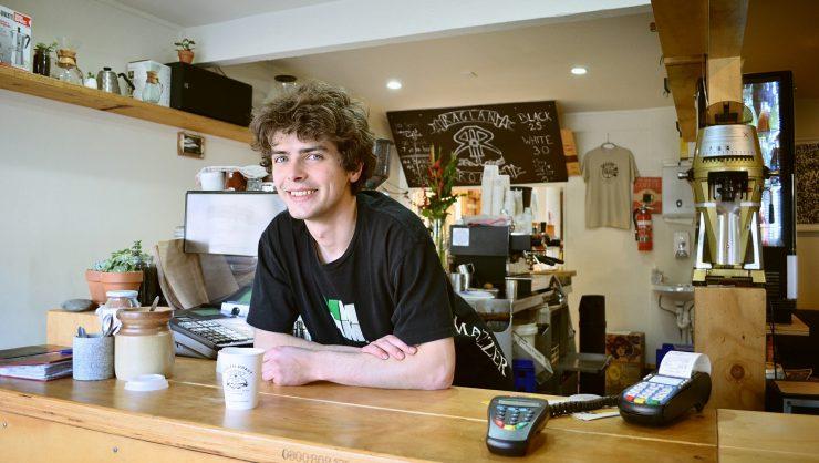 Homem loiro está atrás de um balcão em uma cafeteria. Ele parece ser dono do estabelecimento. Na banca, duas máquinas de cartão de crédito presentes.