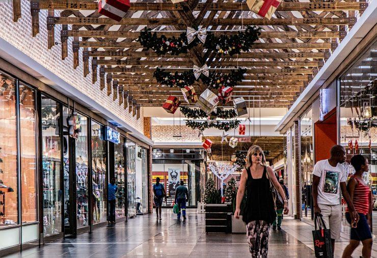 Imagem mostra o corredor de um shopping. As lojas estão decoradas para o período natalino. Vários consumidores passam com sacolas.