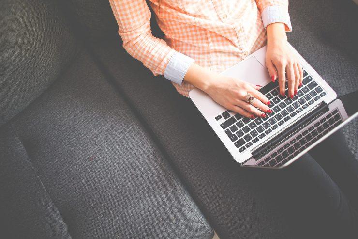 Imagem mostra uma visão aérea de uma mulher utilizando o notebook. Ela está com as mãos sobre as teclas.