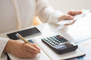Imagem mostra uma mão feminina calculando contas. Simula endividamento.