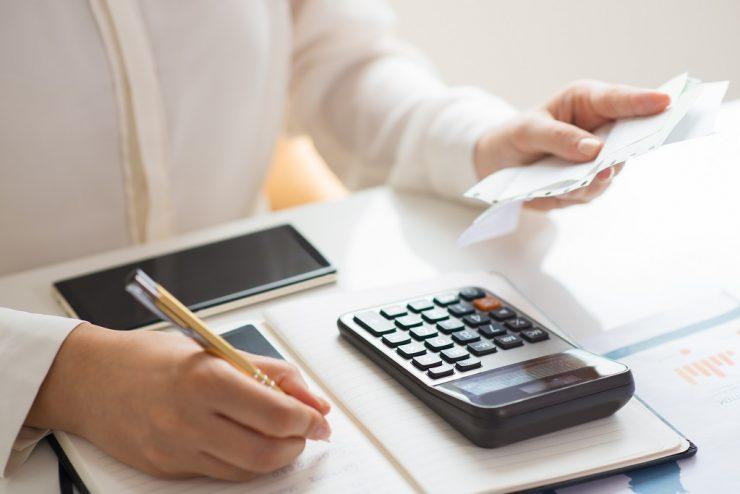 Imagem mostra uma mão feminina calculando contas. Simula dívidas