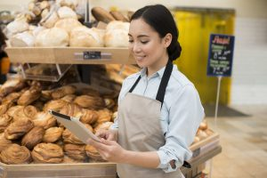 Imagem mostra vendedora olhando para um tablet, dentro de uma padaria. Ilustra um bom atendimento