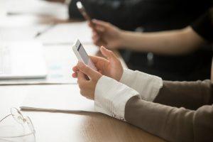 Foto mostra duas mãos femininas segurando um celular, em cima de uma mesa. Ilustra a pesquisa por serviços.