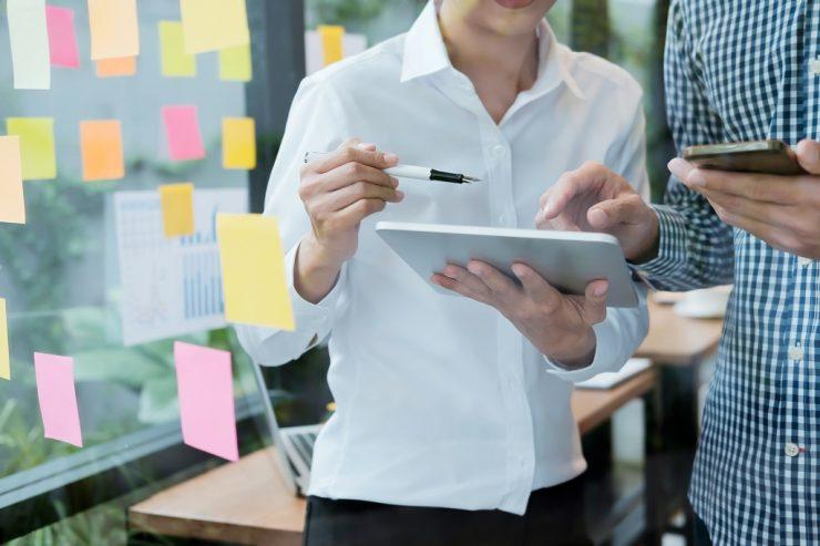 Imagem mostra duas pessoas ao lado de um quadro transparente cheio de post-its. O foco está no tablet. Ilustra um canvas.