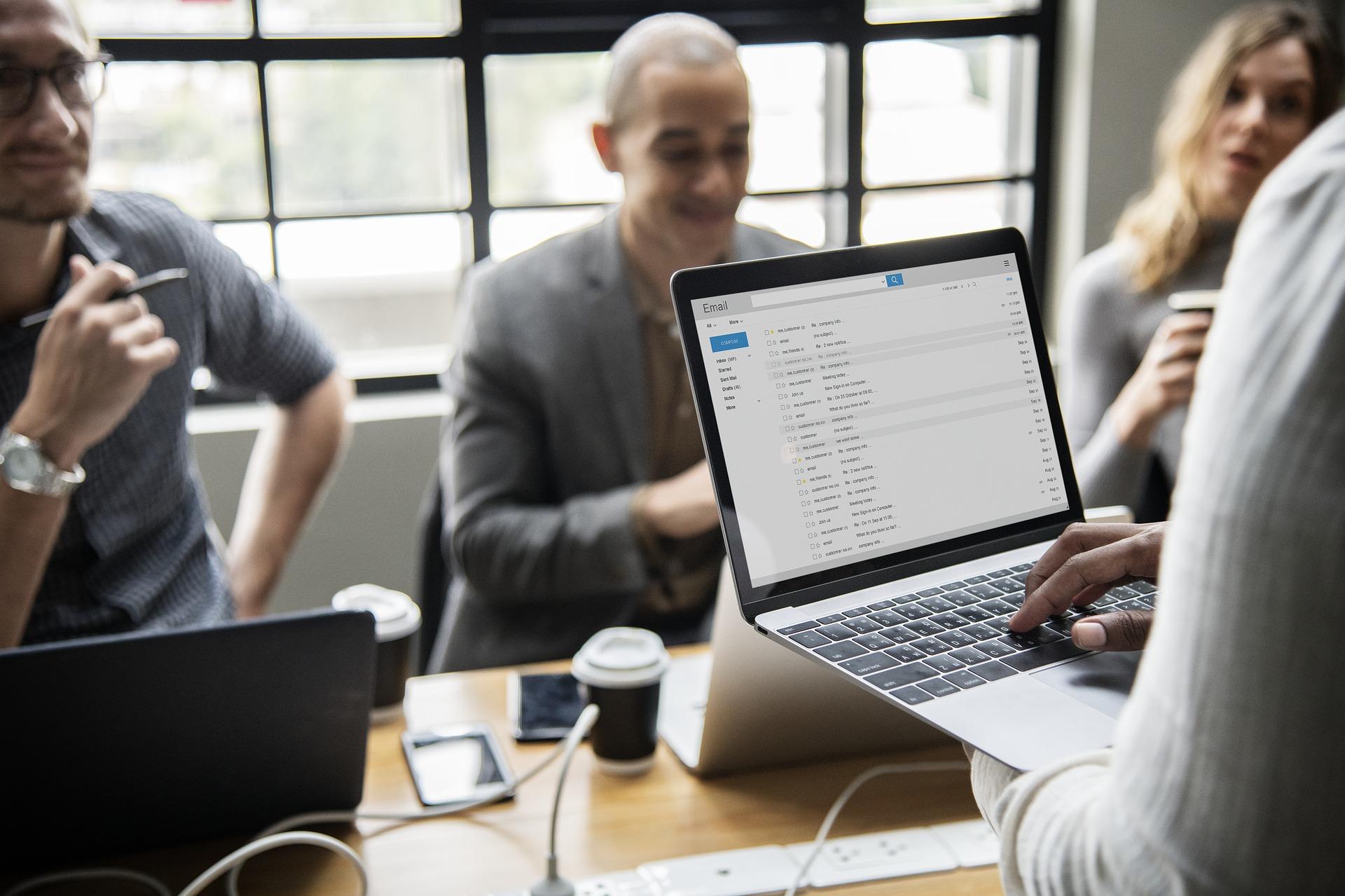Imagem mostra simulação vendas para o governo. Mulher segura um notebook, enquanto ao fundo 2 homens e uma mulher se reúnem.