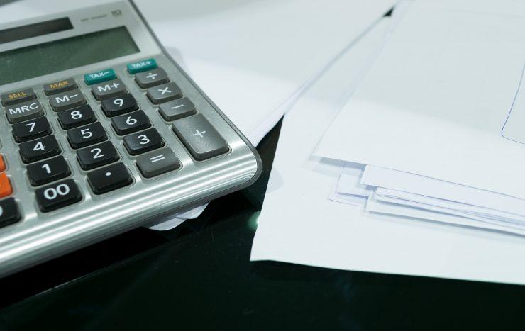 Imagem mostra uma calculadora ao lado de uma série de papéis. Ilustra a prática de investimento.