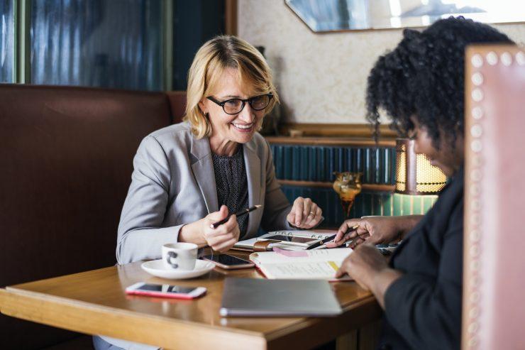 Foto mostra duas executivas conversando em uma mesa de café. Uma é caucasiana e loira e a outra é negra e com cabelo escuro. Estão apontando para finanças. Simulam Empresas Simples de Crédito