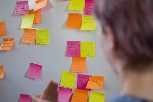 Imagem mostra mulher olhando para uma parede cheia de post its coloridos. Ilustra o processo de branding