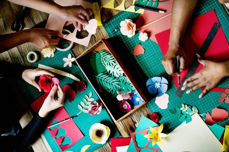 Foto mostra três pares de mãos produzindo diferente estilos de artesanato.