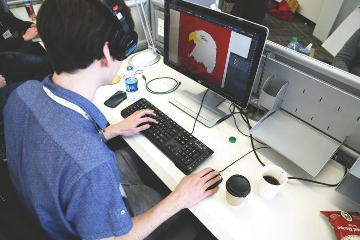 Homem branco utiliza o computador. Na tela, uma imagem de águia em um programa de imagens. Parece estar em uma aceleradora.