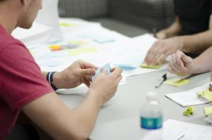 Imagem mostra as mãos de três pessoas trabalhando sobre uma mesa cheia de post-its. Eles parecem utilizar a metodologia lean